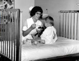 1965.1.3 Graham Hospital School of Nursing student feeding pediatric patient