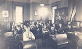 Photo of school classroom with 21 children sitting at desks and one male teacher.
