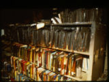 A book case full of charred books, after the Joliet Public Library was firebombed on April 19,...
