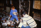 Joliet Public Library staff members Jean Riffel and Roger Gambrel removing damaged books after the...